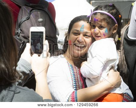 NEW YORK - APR 30 2016: Spectators celebrating with colorful powder on their faces take pictures with their cellphones at Holi Hai Festival of Colors hosted by NYC Bhangra in New York April 30 2016.
