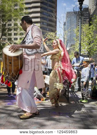 NEW YORK - APR 30 2016: A dancer and drummer from NYC Bhangra perform in traditional clothing in the crowd at the Holi Hai Festival of Colors in Dag Hammerskjold Plaza in New York April 30, 2016.
