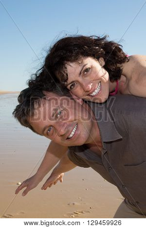 Happy Piggybacking Couple Smiling And Have Fun
