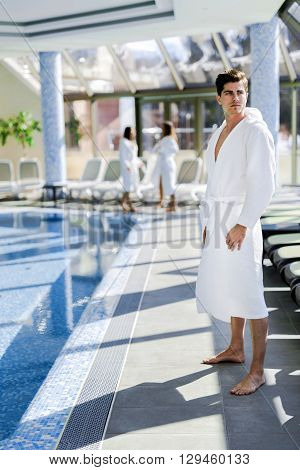 Man standing next to a pool in a robe and relaxing