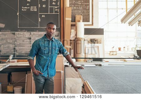 Serious young designer of African descent looking at the camera while standing casually in his studio workshop