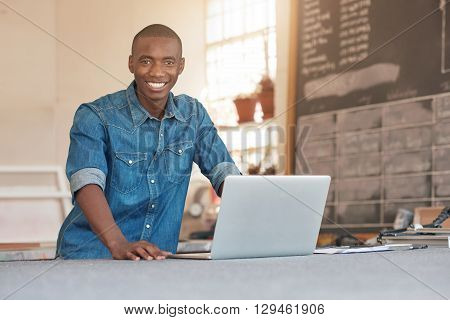 Portrait of a handsome young entrepreneur of African descent smiling at the camera in his studio, with his laptop open in front him