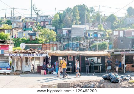 KNYSNA SOUTH AFRICA - MARCH 5 2016: Unidentified people in an early morning scene of shacks and informal businesses in a township in Knysna. Several shacks are visible in the back