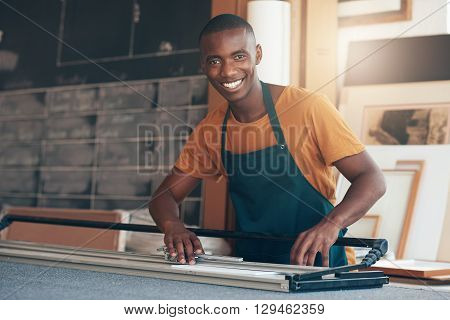 Portrait of a young African craftsman pausing to give the camera a handsome smile, while working with skill using a cutting tool in a picture framing workshop