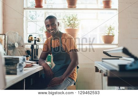 Portrait of a handsome young African artisan and craftsman, wearing an apron and sitting at h studio desk in his workshop, smiling at the camera with beautiful natural light coming in through windows