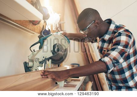 Young aritsan of African descent working with expertise in a woodworking workshop, handling a circular saw, and wearing safety goggles