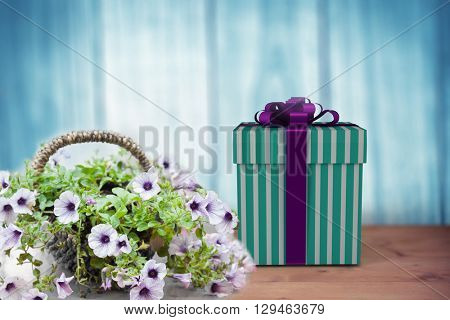 Blue and silver gift box against a wall