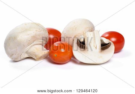 Champignons or white mushrooms and cherry tomatoes, isolated on white background.