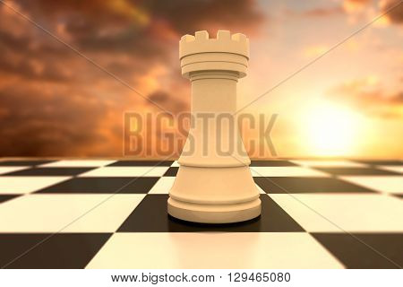 White rook on chess board against sun shining