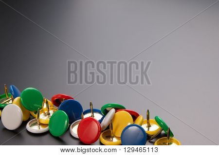 Group Of Colorful Push Pins On Black Board Background.