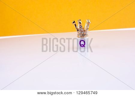Crown on letter cube on a yellow and white background