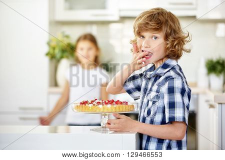 Boy tasting from fruit cake at birthday party in the kitchen