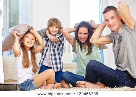 Hapy Family with children making pillow fight at home in the living room
