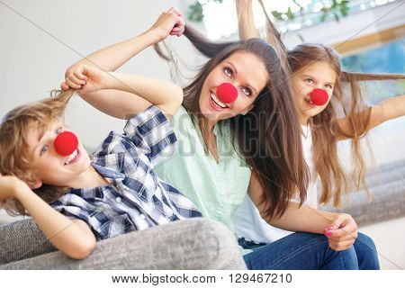 Mother and children with red noses having fun at home