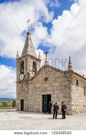 Vila Nova de Famalicao, Portugal. September 06, 2015: Typical small parish church during mass with men waiting outside. Avidos, Vila Nova de Famalicao, Braga, Minho, Portugal
