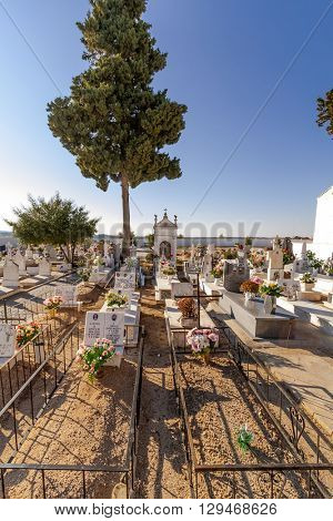Crato, Portugal. December 12, 2015: Poor people graves in a typical Catholic cemetery with the graves decorated with flowers in the interior south of Portugal.