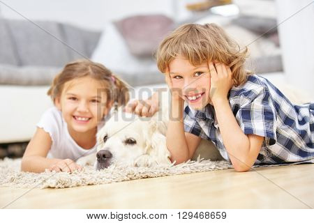 Boy and girl playing with Golden Retriever dog at home
