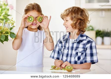 Two happy kids having fun with kiwi in a kitchen