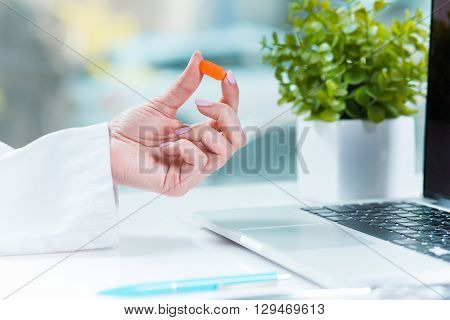 Healthcare and medical concept. Doctor with pill in hospital