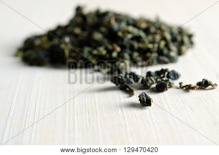 Piles of dried green tea leaves isolated on wooden board background