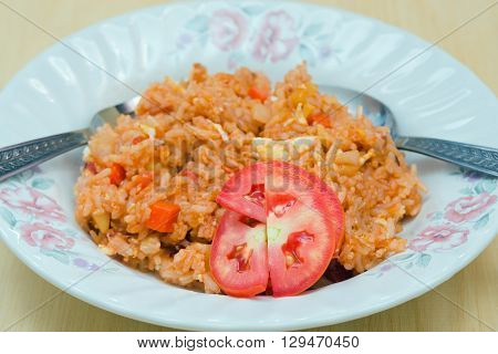 Fried rice with tomato and vegetables with fork and spoon