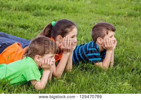 Three smiling kids lying together on green grass field