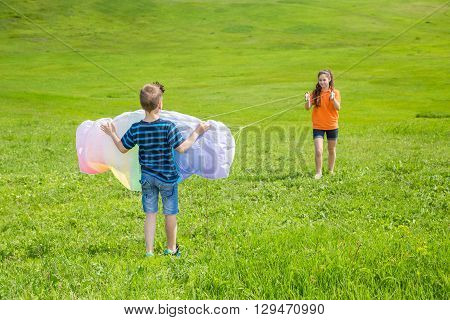 Two kids runs a colorful kite on the green lawn