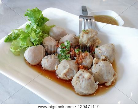 Pork balls in white plate with spicy dipping in Thai restaurant.