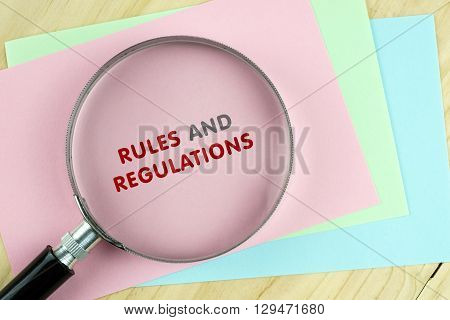 Word Rules And Regulations On Colored Paper With Magnifying Glass.