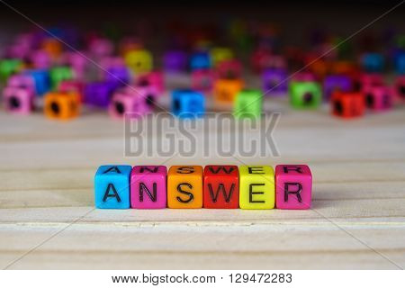 Arrangement of word ANSWER with colorful beads on wooden table.