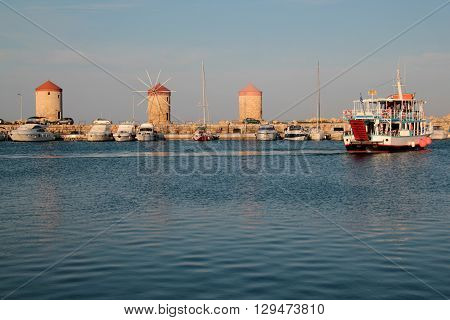 the windmills and the ship close to the island of Rhodes