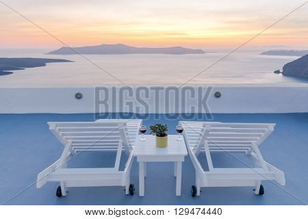 View from the terrace in Fira. The picturesque sunset over the sea and the caldera.