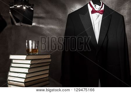 Whiskey glass on the books over hanging tuxedo background.