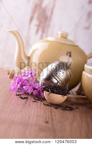 Wooden Spoon With Pile Of Dry Tea And Tea Set