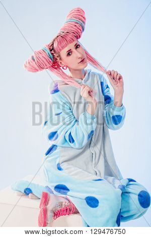 Funny girl in blue pajamas on white background