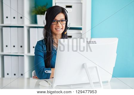 Female Operator With Headset Smiling At Camera In Call Center