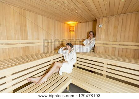 Women Relaxing On The Bench In The Sauna