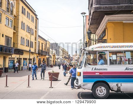 Lima, Peru - October 11 2014 - A typical Lima bus crossing in front of Jiron Trujillo street in downtown Lima Peru.