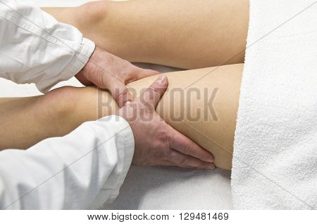 physical therapist providing leg massage to woman in office