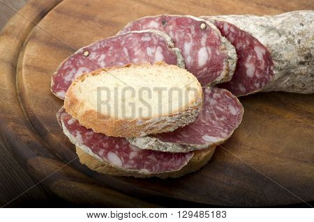 wooden cutting board with salami and bread