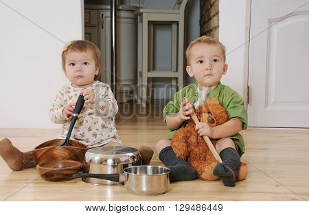 two little kids boy and girl sitting on the kitchen floor playing with pots and pans kids have fun happy kids concept
