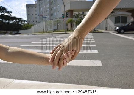 Photography hands of an adult and child in the background crosswalk.