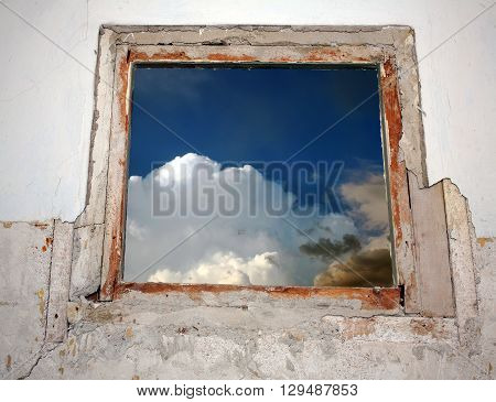 Old ruined window which shows the sky with clouds