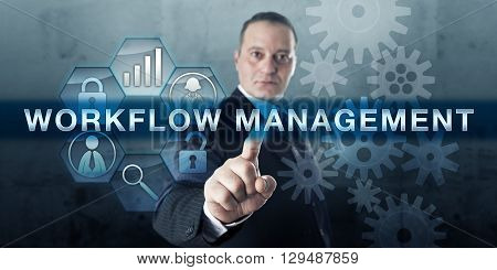 Manager pressing WORKFLOW MANAGEMENT on a virtual touch screen interface. Business concept for the structured organization of resources processing of information and performance monitoring software.