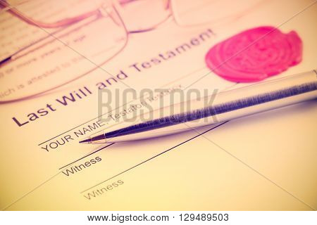 Vintage / retro style : Last will and testament sealed with wax seal stamped / embossed with alphabet letter B. With a blue ballpoint pen and eye glasses on a table.