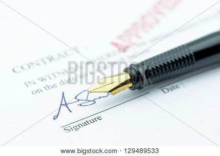 Fountain pen with a signature on an approved contract.
