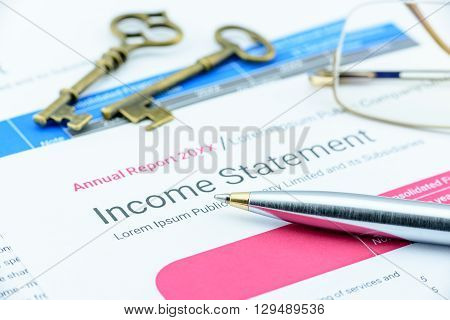 Blue ballpoint pen on a corp's income statement with two antique brass keys and eye glasses. Analysis concept for financial adviser for a long term investment strategy and sustainable growth.