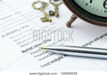 Blue ballpoint pen on a financial ratios analysis check lists with an antique clock and two vintage brass keys. Financial business and investment analysis concept.