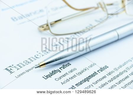 Blue ballpoint pen and eye glasses on a company's financial analysis check list. An investment for long term sustainable growth concept.