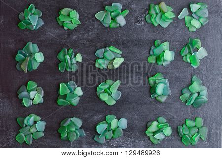 small green pieces of glass polished by the sea closeup on black background